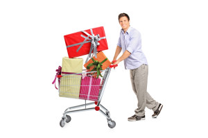 Young man pushing a shopping cart full with gifts